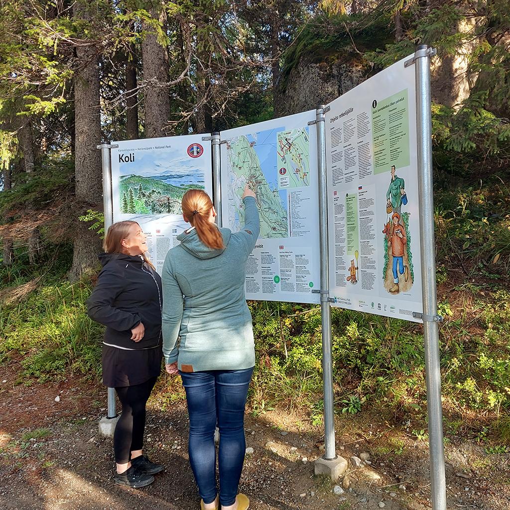Kuva: Mika Kareinen. Kaksi naishenkilöä katsoo karttaa luontoympäristössä.