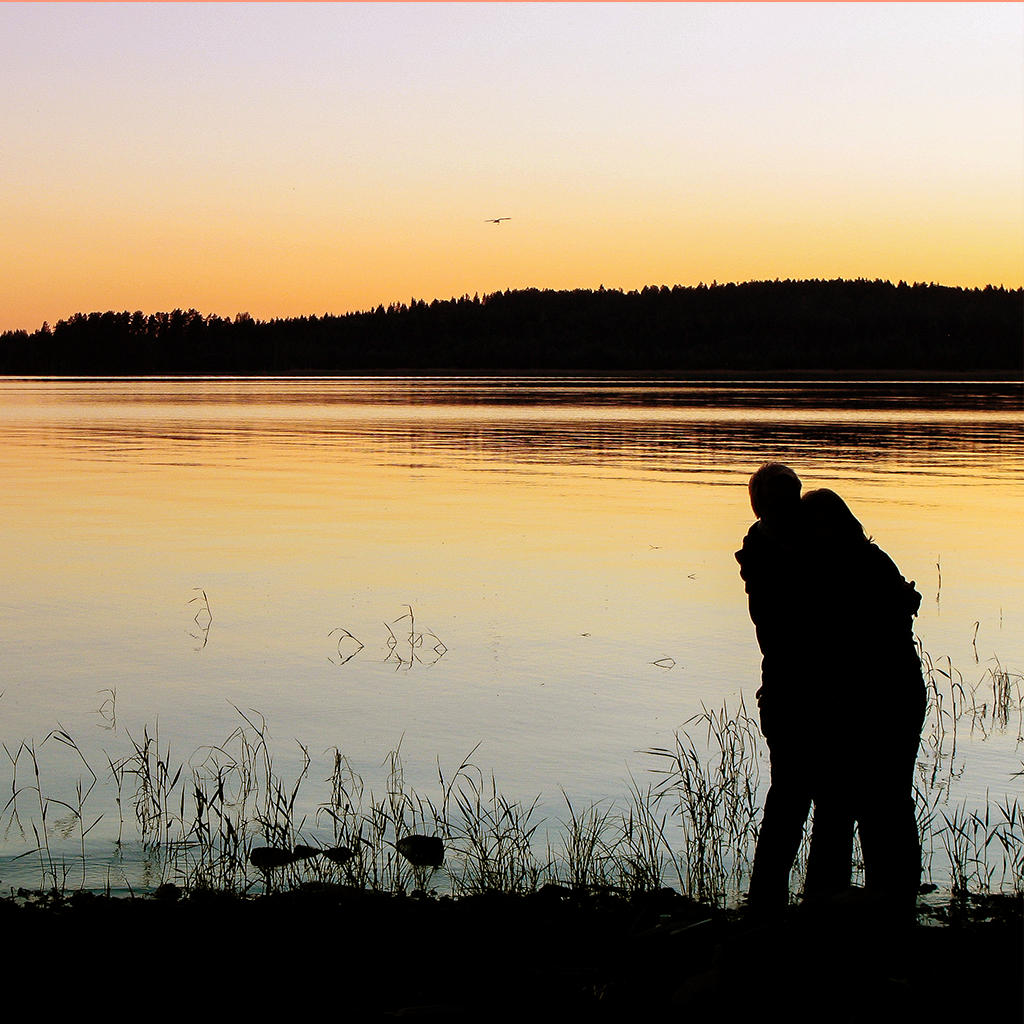 Kuva: Mika Kareinen. Pariskunnan silhuetti ilta-auringossa järven rannalla.